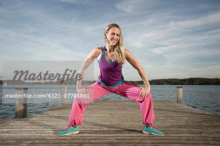 Woman dancing Zumba on jetty, Woerthsee, Bavaria, Germany