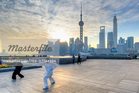 People practicing Kung Fu along the promenade at The Bund at sunrise, view of Pudong skyline, Shanghai, Shanghai Shi, Zhonghua, China