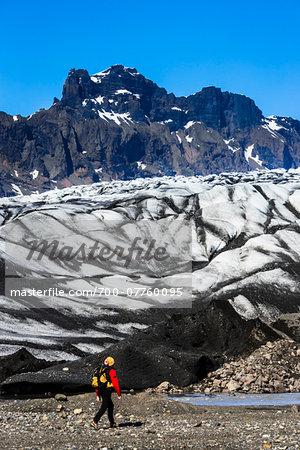 Hiker next to glacier with mountains in background, Skaftafellsjokull, Skaftafell National Park, Iceland