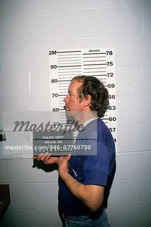 1990s MAN UNDER ARREST HAVING POLICE MUG SHOT PROFILE PHOTOGRAPH TAKEN