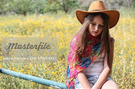 Sullen girl in cowboy hat sitting on fence gazing down