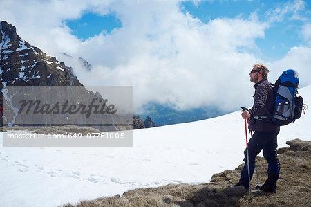 Mature man standing in snow, Bucegi Mountains, Transylvania, Romania