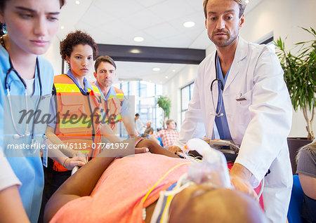 Doctor, nurses and paramedics examining patient in hospital
