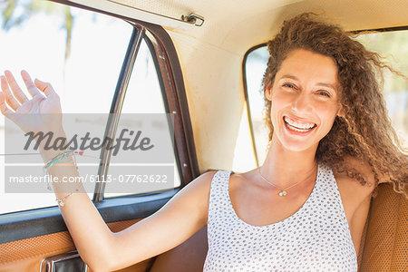 Woman feeling breeze from backseat car window