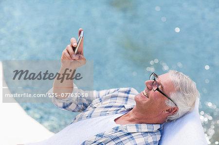 Senior man using cell phone at poolside