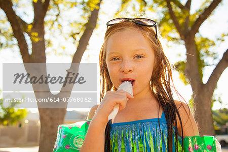 Portrait of girl eating ice lolly in garden