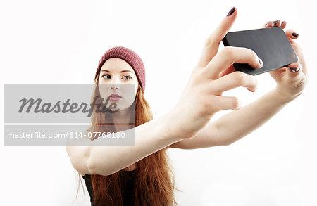 Studio portrait of young woman making selfie on smartphone