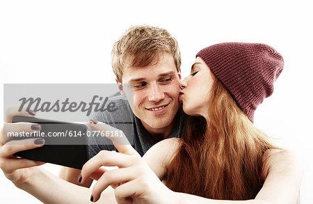 Studio portrait of young couple taking selfie on smartphone