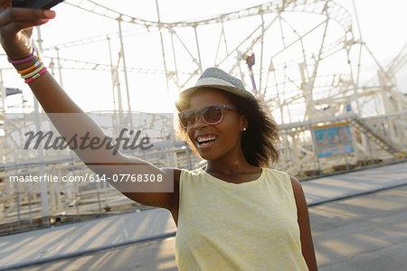 Young woman taking self portrait on smartphone, Coney Island, Brooklyn, New York, USA