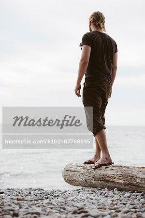 Man standing on log on beach, Gotland, Sweden