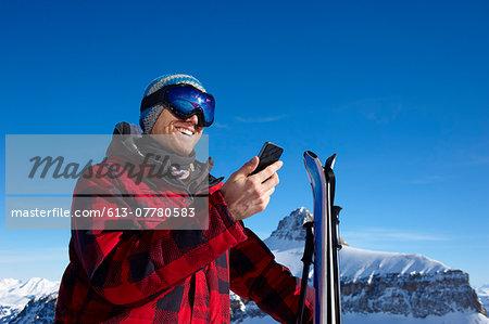 A man using phone in mountain scene.