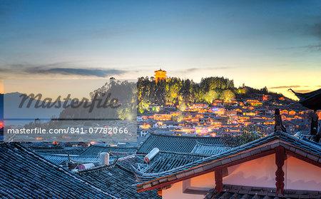 Night falls over Lijiang and Shizishan (Lion Hill with WanGu Tower) while the city lights slowly come to life, Lijiang, Yunnan, China, Asia