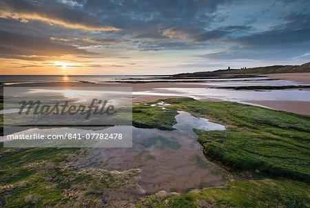 Gorgeous sunrise over Embleton Beach, looking towards Dunstanburgh Castle, Northumberland, England, United Kingdom, Europe