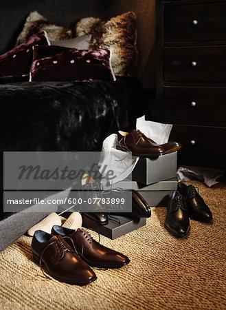 New, men's dress shoes and boxes on floor beside bed in bedroom, studio shot