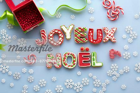 Overhead View of Christmas Sugar Cookies spelling JOYEUX NOEL on Blue Background with Snowflakes