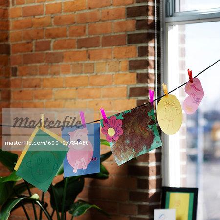 Children's Artwork Hanging on Clothesline by Window