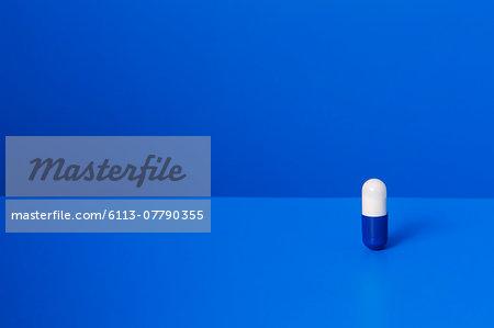 Prescription pill standing upright on blue counter