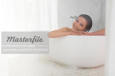 Smiling woman taking bath in modern bathroom
