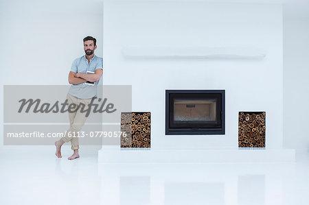 Man leaning on modern fireplace
