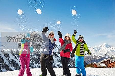 Family throwing snowballs on mountain top