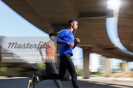 Men running together through city