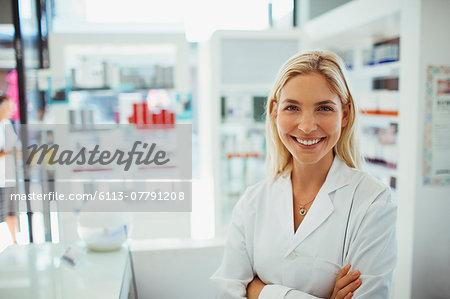 Pharmacist smiling in drugstore