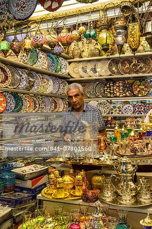 Seller (vendor) of traditional Turkish ceramics, glassware and tea sets in his shop, Grand Bazaar, Istanbul, Turkey, Europe