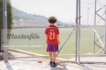 Boy Standing in front of Football Stadium, Valldemossa, Majorca, Spain