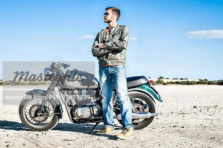 Portrait of young male motorcyclist on arid plain, Cagliari, Sardinia, Italy