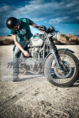 Mid adult man checking motorcycle on arid plain, Cagliari, Sardinia, Italy