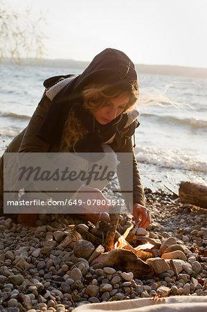 Woman making a fire by seaside