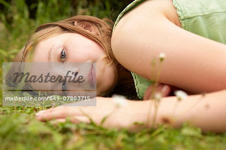 Close up portrait of girl lying on garden grass