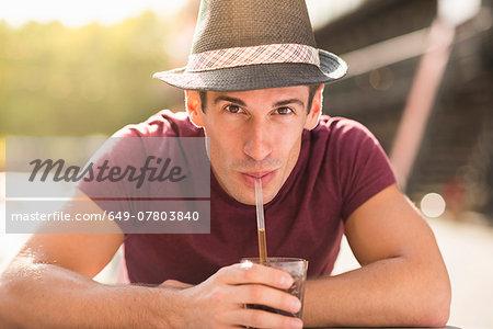 Young man wearing hat drinking through straw