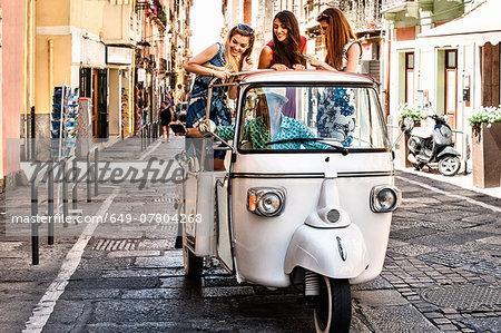 Three young women standing up in open back seat of Italian taxi, Cagliari, Sardinia, Italy
