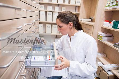 Pharmacist in pharmacy opening medicine file drawer