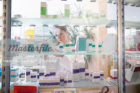 Pharmacist in pharmacy looking at medicine box
