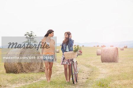 Friends with bicycle walking on field, Roznov, Czech Republic