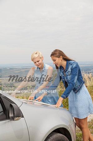 Friends reading map on bonnet of car, Roznov, Czech Republic