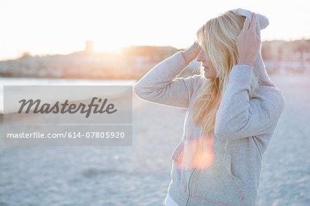 Woman putting hood over head on the beach
