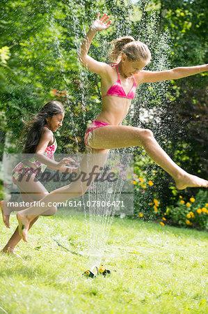 Girls in swimming costume jumping over garden sprinkler