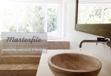 Modern bathroom interior with stone sink and bathtub