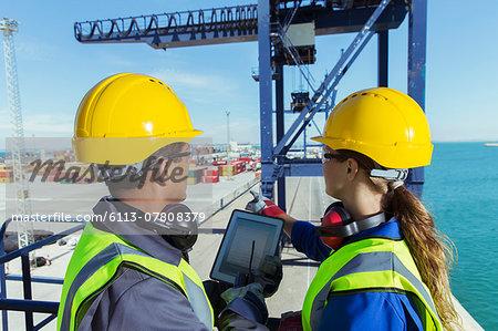 Workers using digital tablet on cargo crane