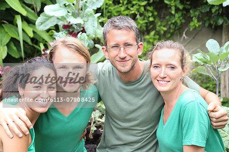 Portrait of four men and women wearing green t-shirts in garden