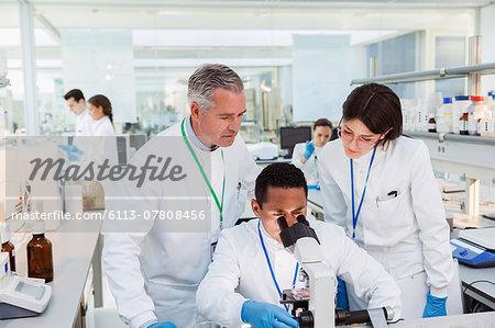Scientists using microscope in laboratory