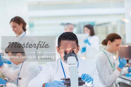 Scientist examining sample under microscope in laboratory