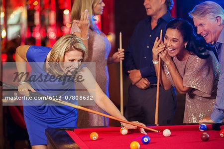 Friends playing pool in nightclub