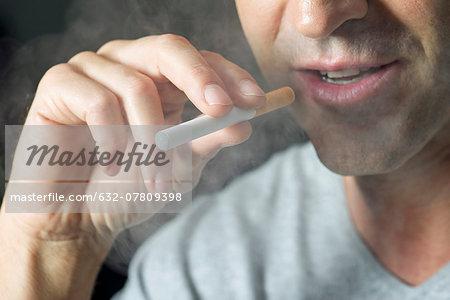 Man smoking electonic cigarette, cropped