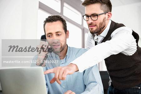 Two men telephone talking computer meeting