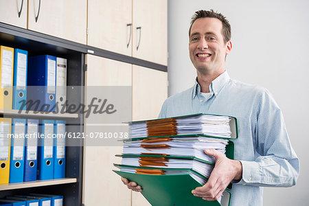 Portrait man carrying pile filing folders