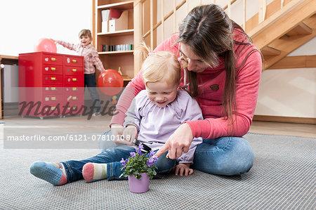 Female educator playing with little girl in kindergarten